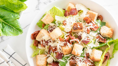 salad with cheese bacon and croutons on a marble countertop