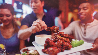 Guy holding a plate of wings